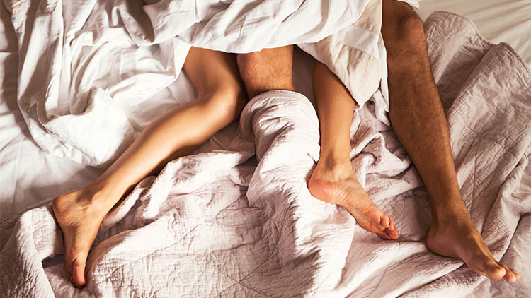 Couple lying in bed under sheets