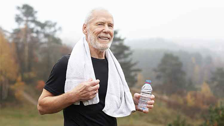 Exhausted elderly male with gray hair and beard drinking water after outdoor exercise and wiping sweat with towel around his neck