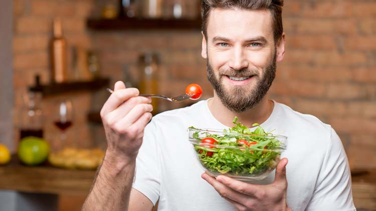 Handsome bearded man in white t-shirt eating salad with tomatoes in the kitchen. Healthy and vegan food concept