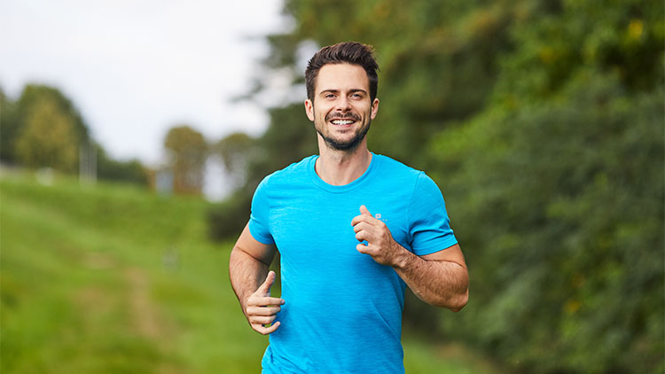 Happy man running in park during summer
