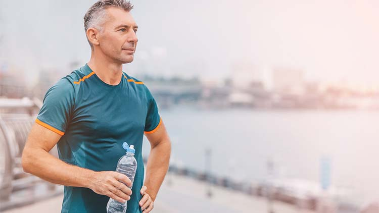 Portrait of healthy athletic middle aged man with fit body holding bottle of refreshing water, resting after workout or running. on the riverside.
