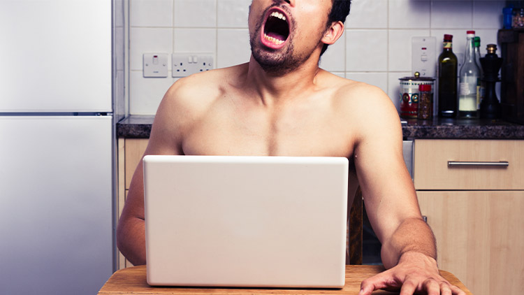Young naked man watching pornography in his kitchen