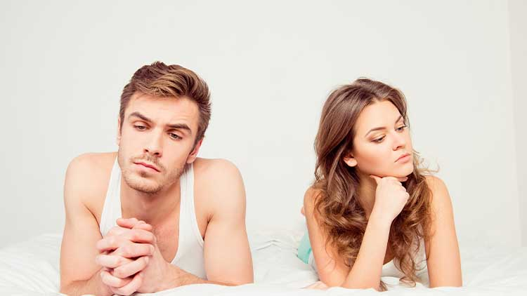Young disconnected couple lying on the bed