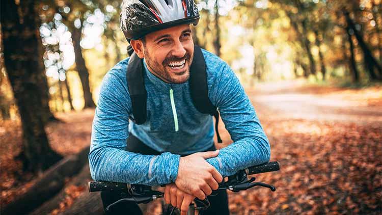 Young man biking through forest