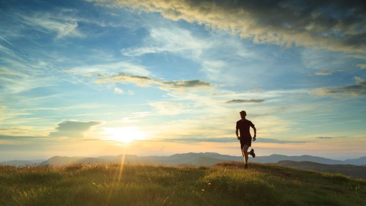 Athlete running through mountains during sunset