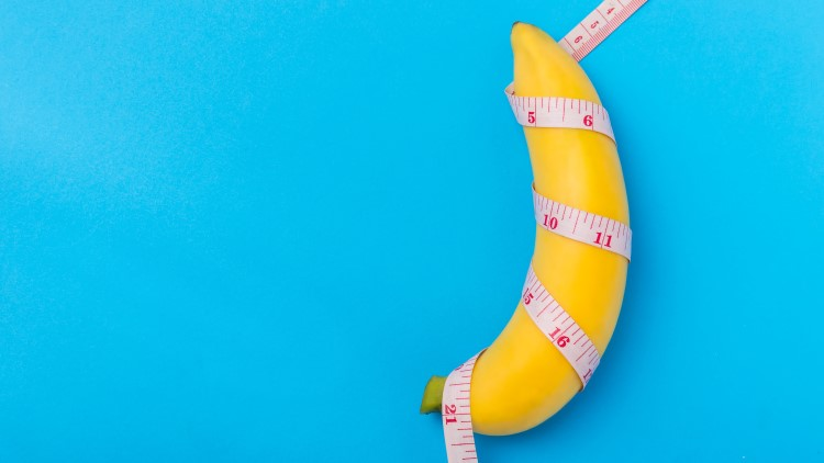 Banana with measurement tape wrapped around on blue background