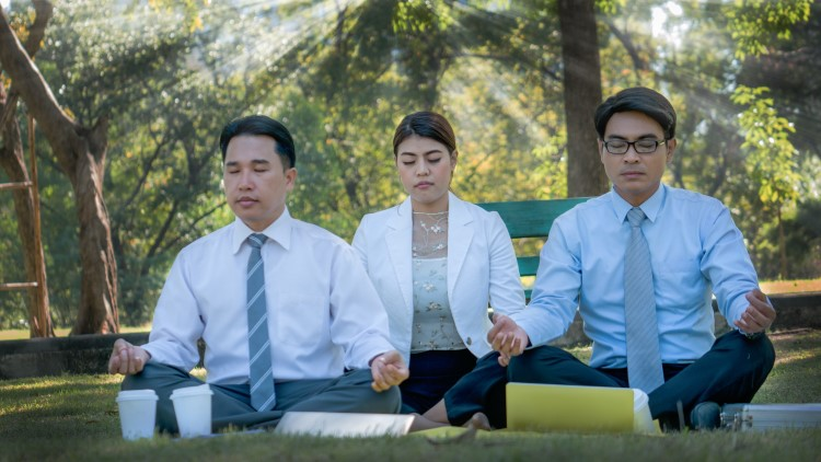 Office workers sat in the park meditating on sunny day