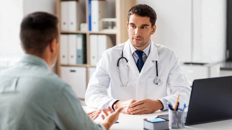 Doctor talking with male patient in medical office
