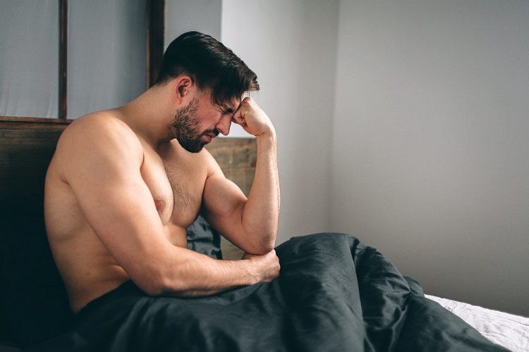 Frustrated man sitting in bed