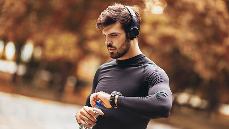 Portrait of young man on a morning jogging in the autumn park, man listening to music with headphones