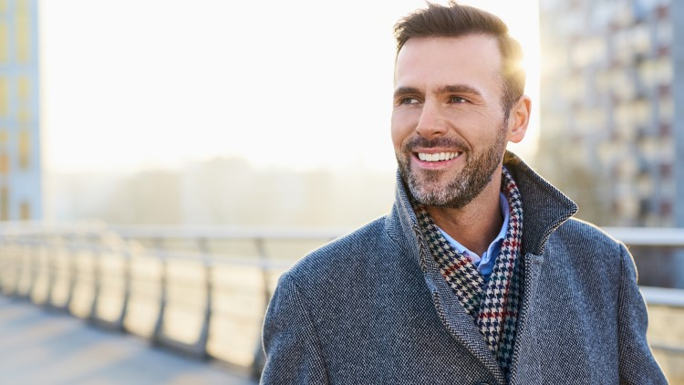 Happy man standing outdoors on sunny winter day