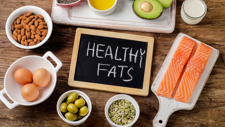 Healthy fats on chalkboard surrounded by suitable foods