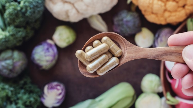 Pills on wooden spoon surrounded by vegetables
