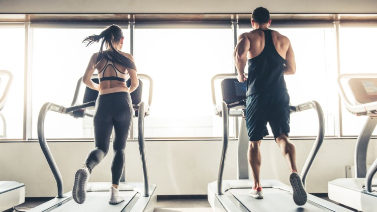 Man and woman running on treadmill in the gym