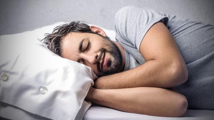 Smiling man asleep alone