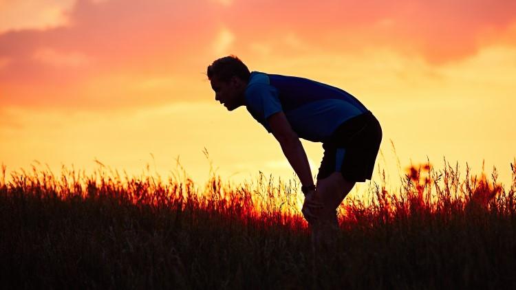 Man catching breath after running through grass at sunset