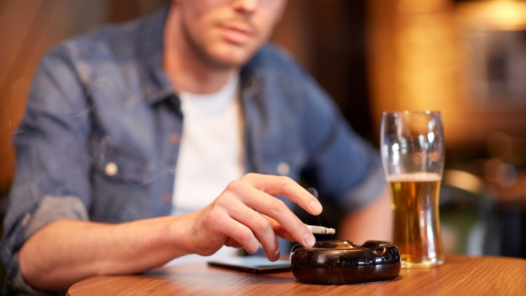 Man drinking and smoking cigarette at table in bar