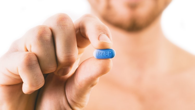 Man holding pill with prep written on pill