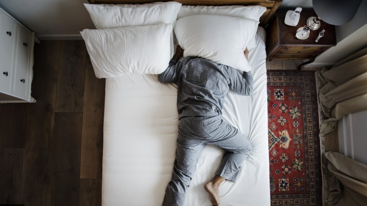 Man drowning out noise pollution holding pillow over his head in bed