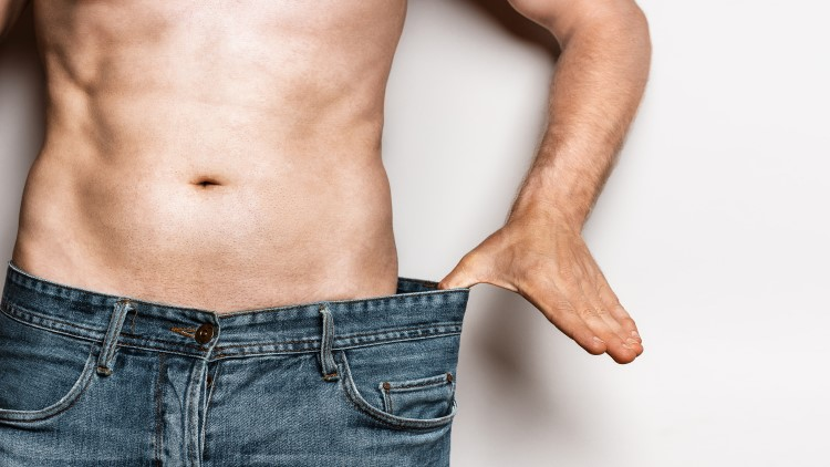 Man pulling waistband of jeans to highlight weight loss