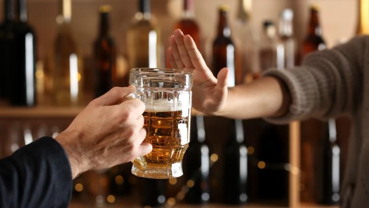 Man refusing to take alcoholic drink in bar