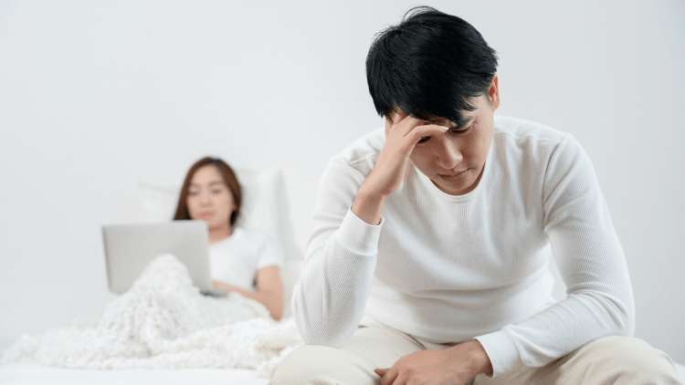 Man sat at edge of bed stressed while partner is in bed using laptop