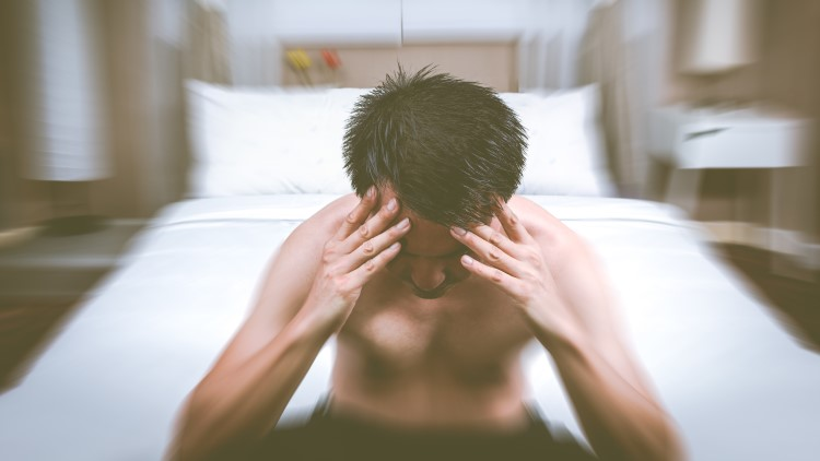 Man sat at end of bed holding head blurred background