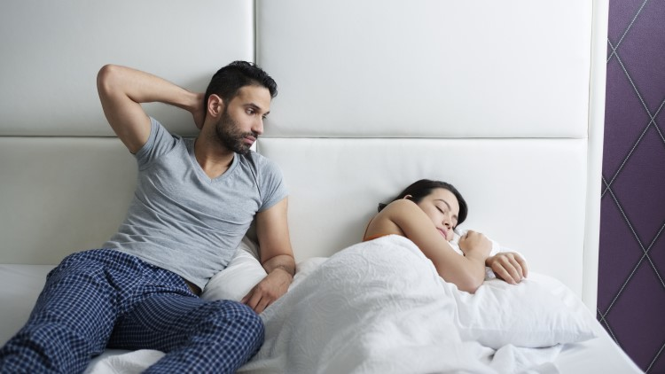 Man sat up in bed looking at partner asleep