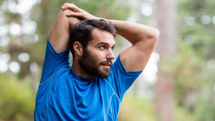 Man stretching arms in forest