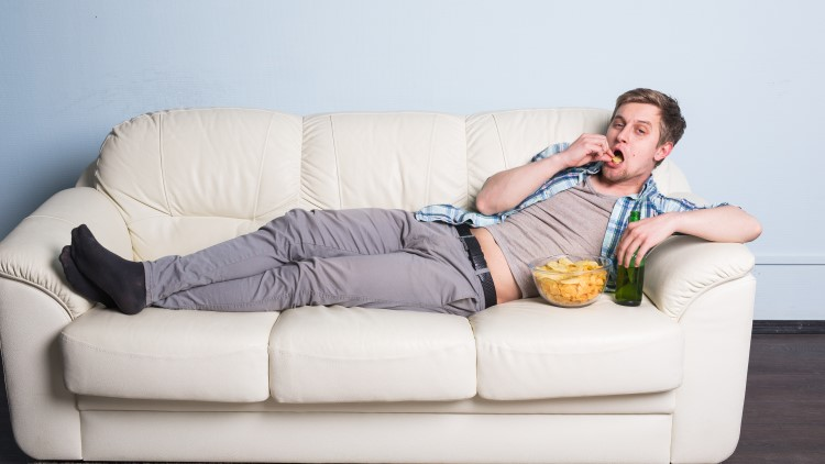 Man with beer and chips watching TV on sofa
