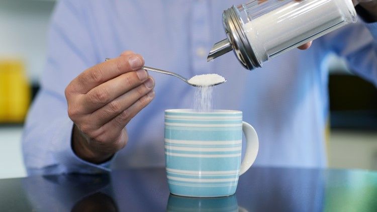 Mature man adding sugar to hot drink