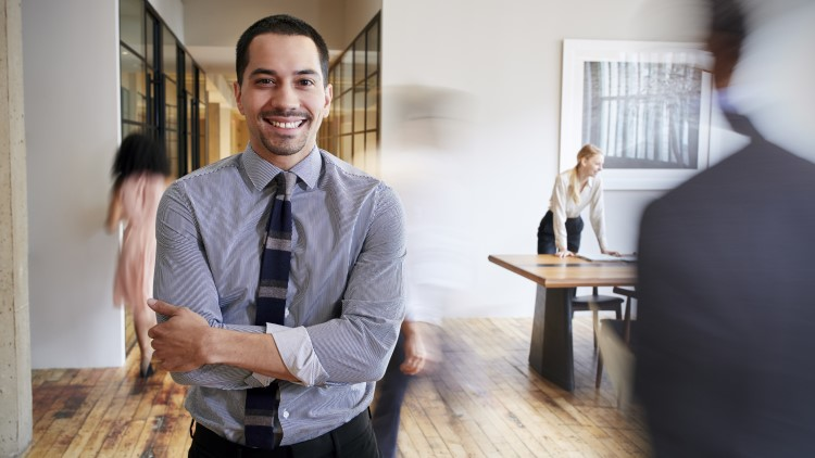 Young Hispanic man in busy office