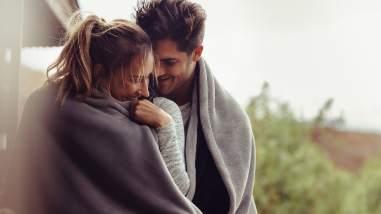 Romantic couple wrapped in blankets outdoors
