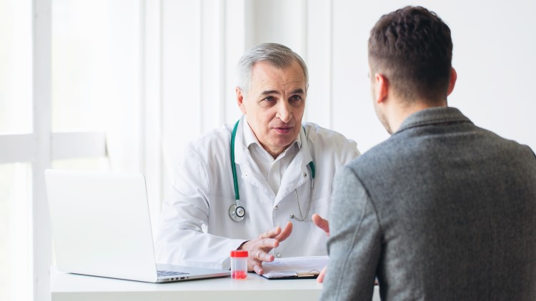 Senior doctor consulting with young male patient