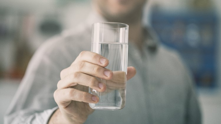 Smiling man holding glass of water