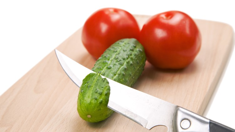 Two tomatoes and one chopped cucumber on cutting board