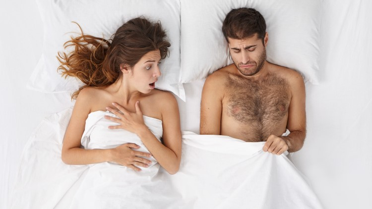 Woman looking shocked at man's penis under bedsheets