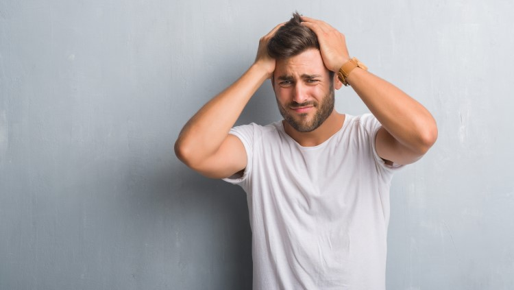 Young man holding top of head looking stressed out