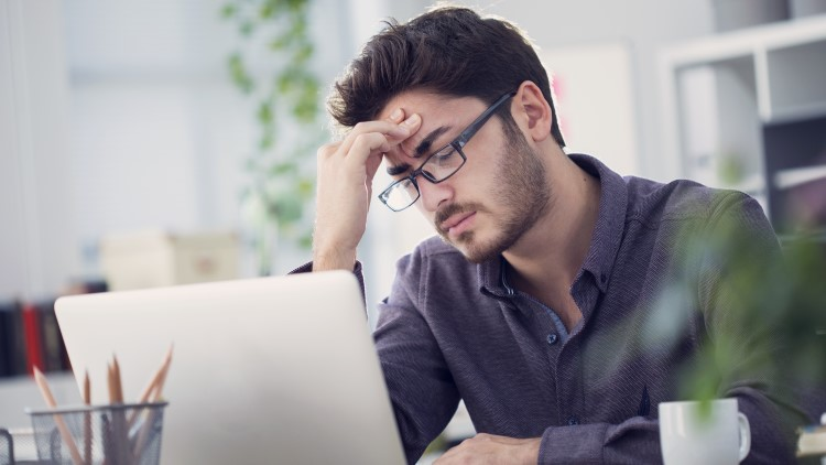 Young man working on laptop with headache